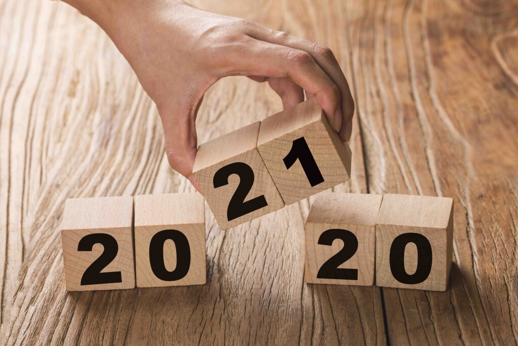 Hand flips a block changing 2020 to 2021. New year beginning. Ho